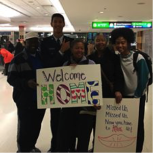 USAFA Cadet arrival home with signs at an airport.